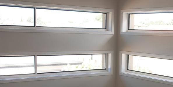 Interior view of a white room with four narrow horizontal windows