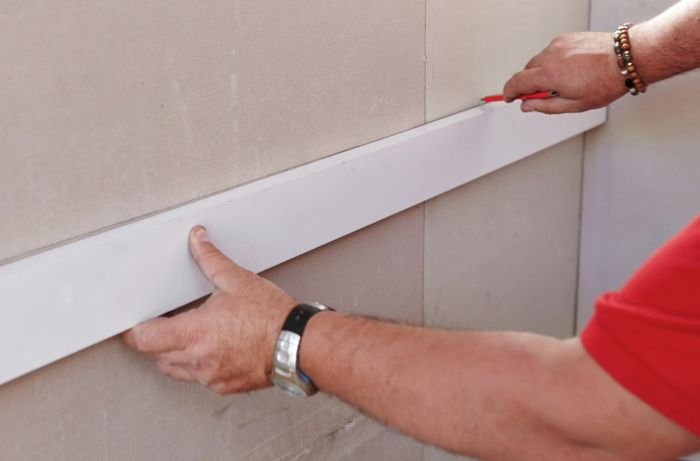 A wall being marked with a pencil by a Bunnings team member