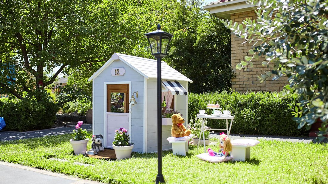 A painted and decorated cubby house with potted plants, a teddy, a doll and a tea set