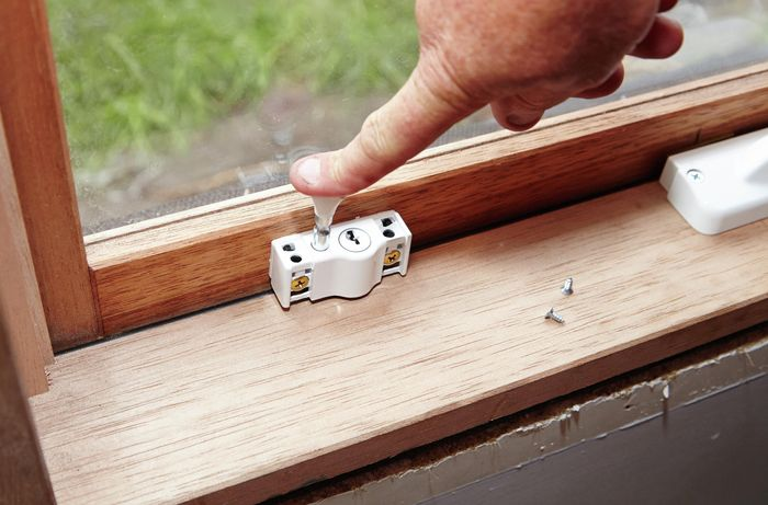 A person pushing down on the bolt of a window lock