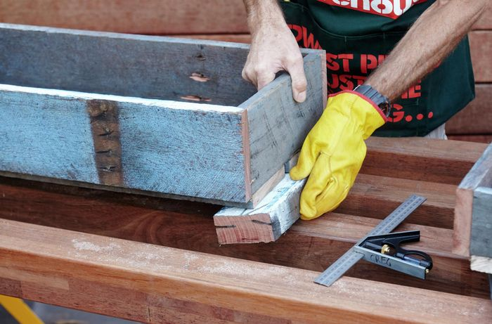 Feet being attached to the bottom tier of a herb planter by a Bunnings team member