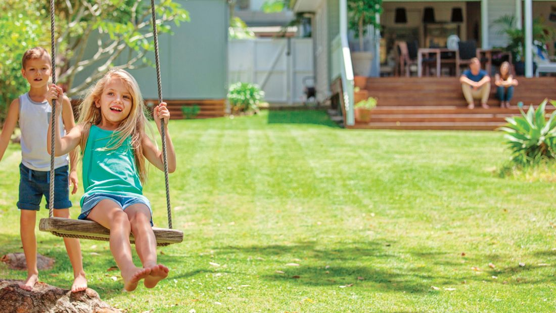 Children playing on a swing with the lawn well maintained