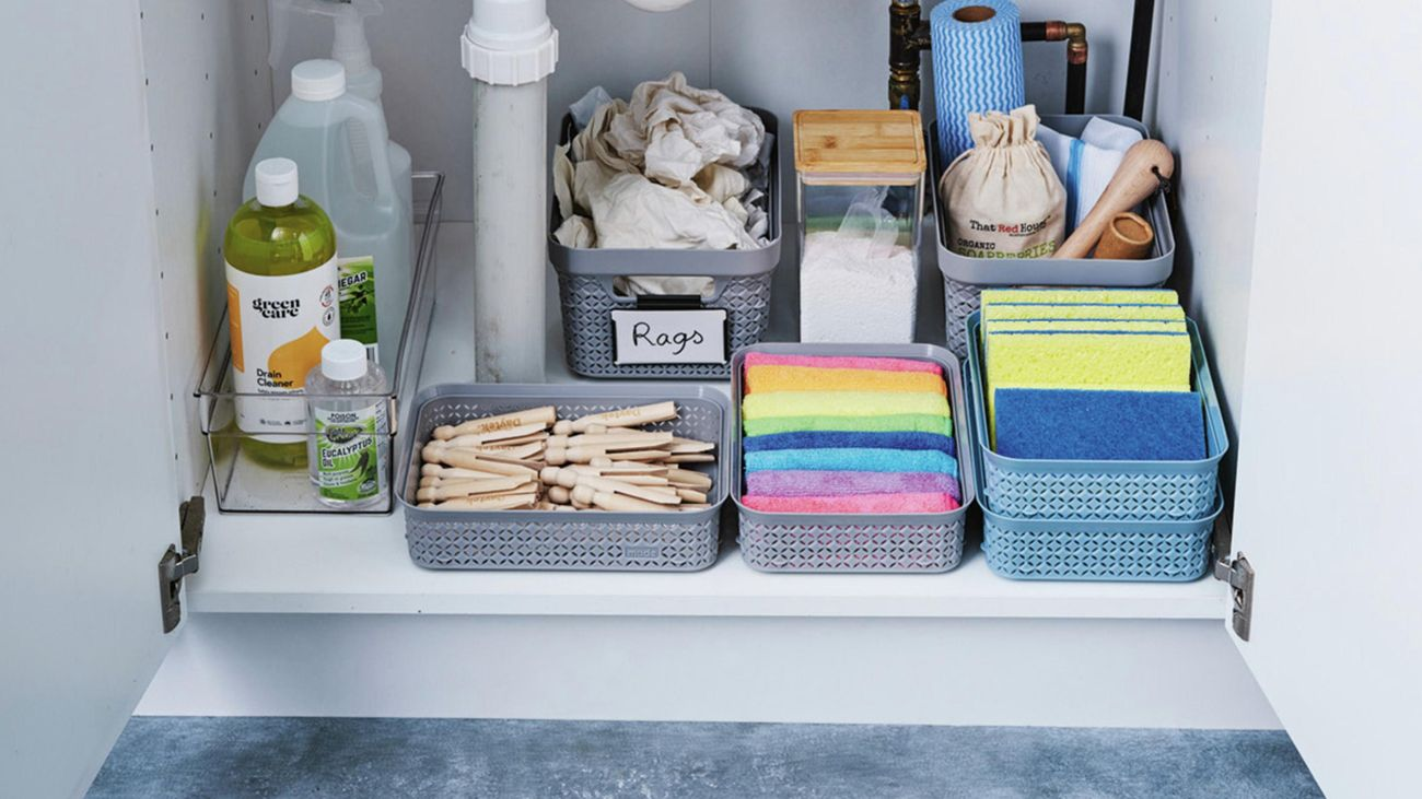 Close up of a vanity cabinet with doors opened showing organised cleaning products and sponges in basket organisers.