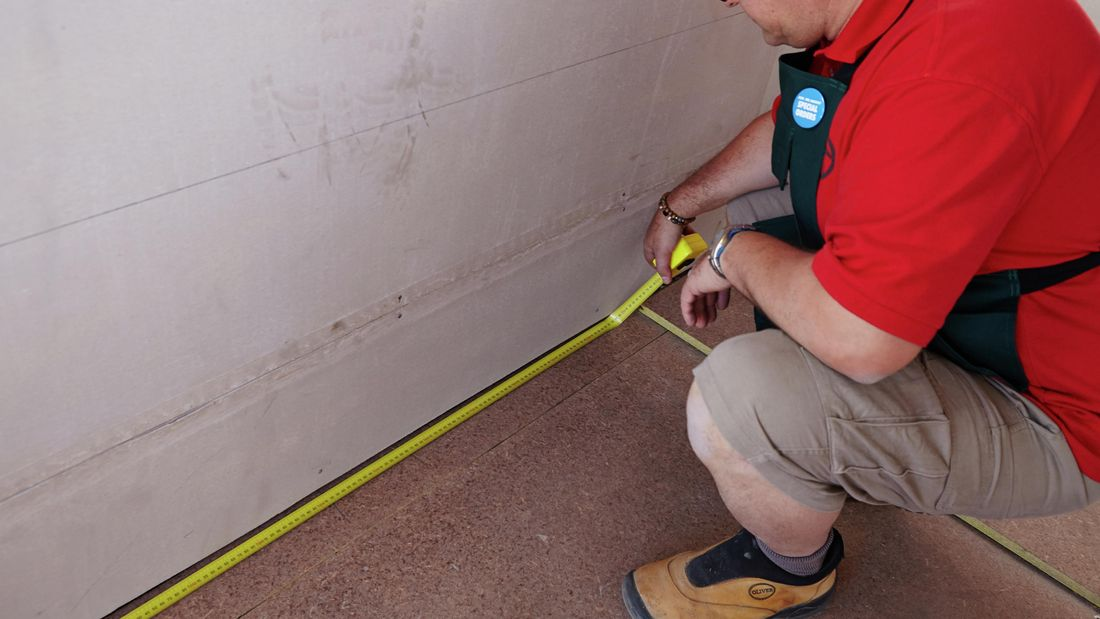 A bare floor being measured by a Bunnings team member with a tape measure