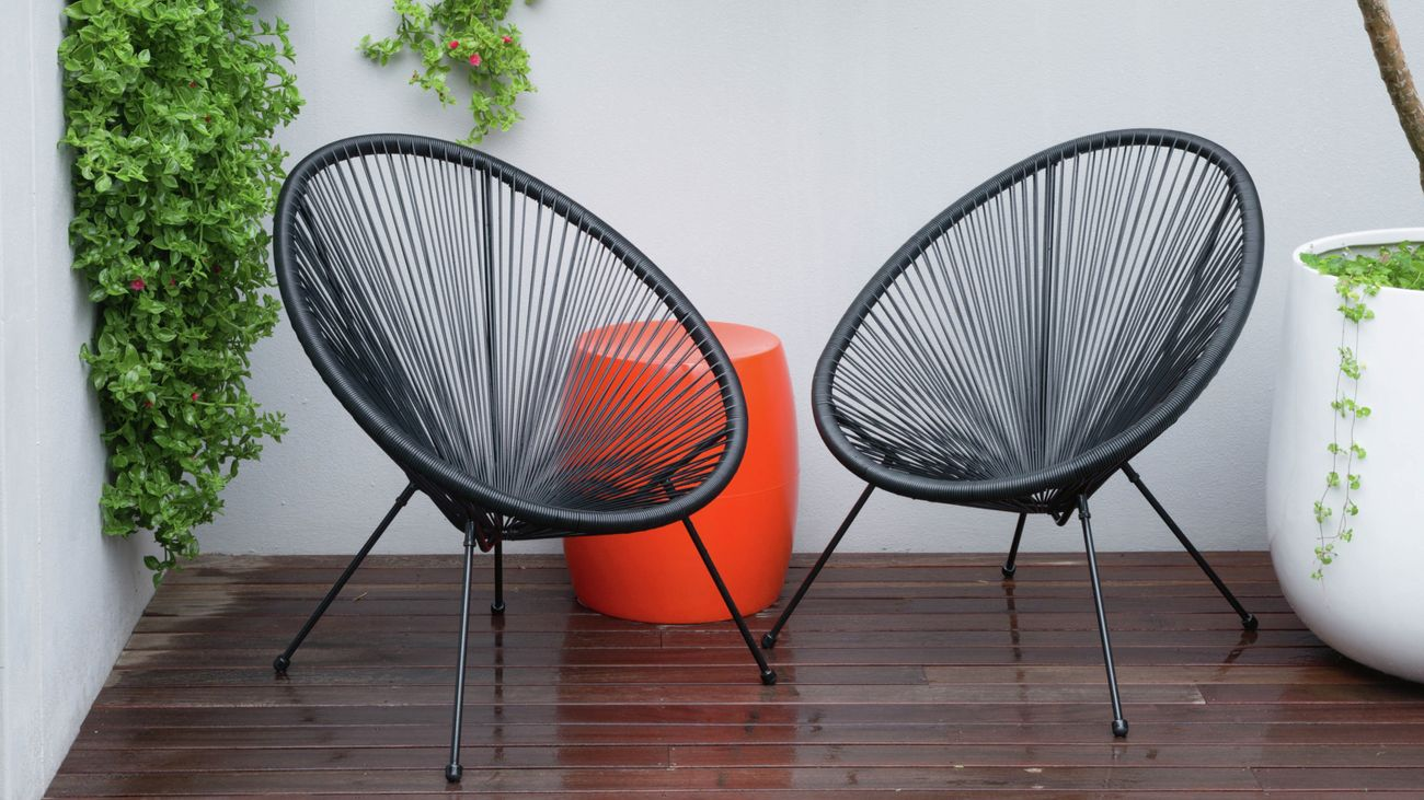 Two black verna acapulco chairs sit opposite eachother on a wooden deck in a small courtyard