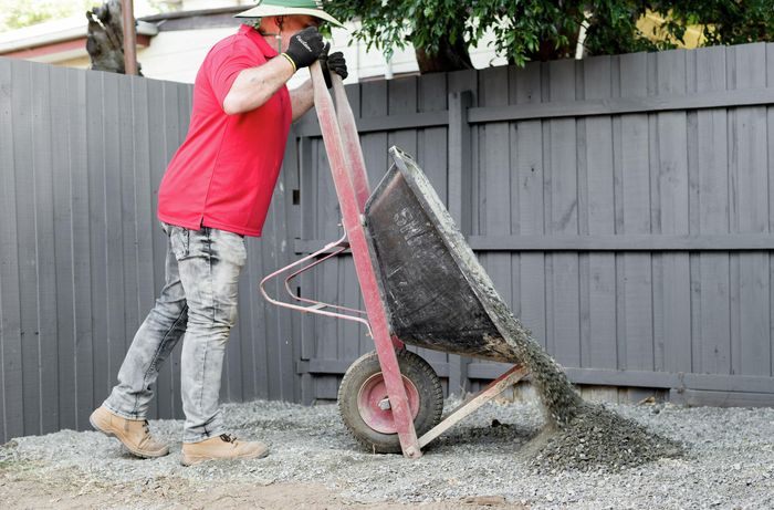 Person in a backyard emptying gravel out of a wheelbarrow.