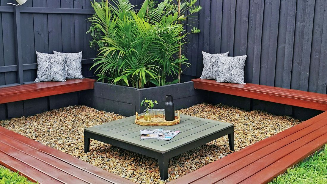 A sunken sitting area in a garden with timber bench seats around a low table set in pebbles