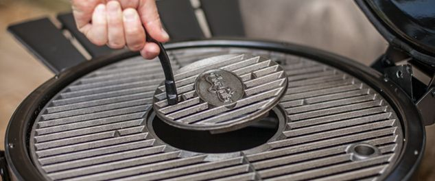 Person removing grilling plate from bbq