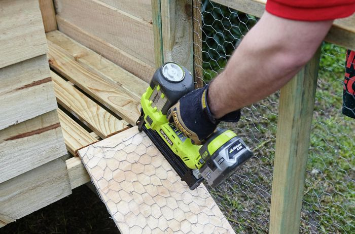 The ramp up to a raised level of a chicken coop being nailed down by a Bunnings team member with a nail gun