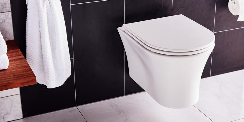 bathroom with black tiles and white toilet