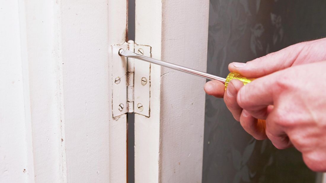 Person unscrewing screw in door hinge.