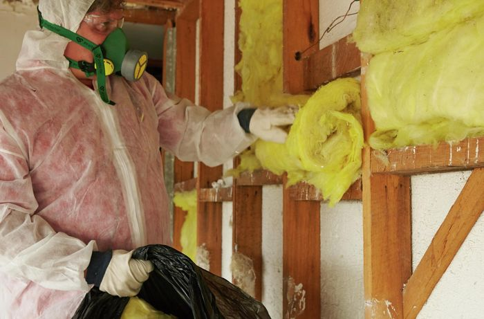 A person wearing protective gear removing insulation batts from a stud wall frame