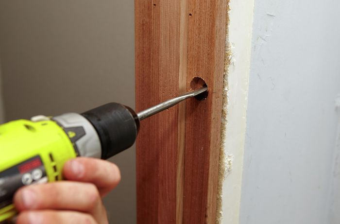 A cavity being cut into a doorframe for a door latch