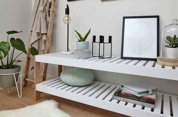 Timber slat shelving unit with books, lamp and indoor pot plants