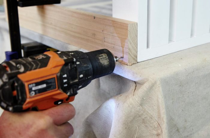 Person attaching table legs to table using drill