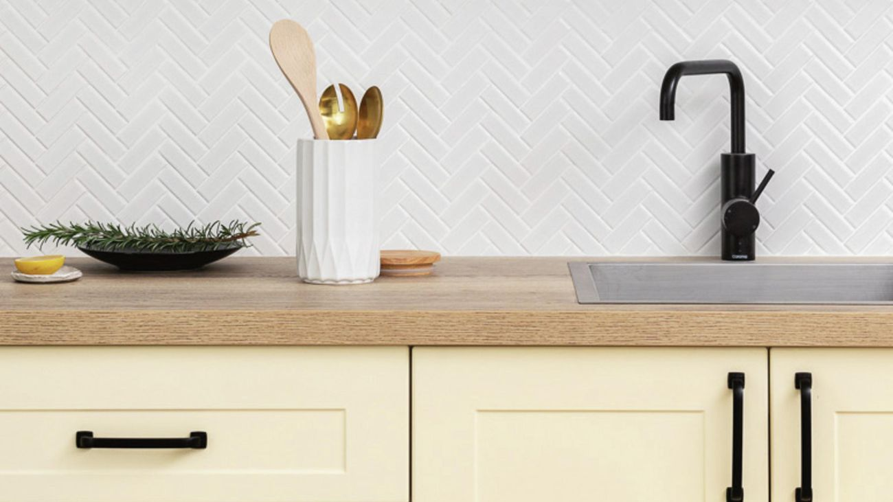 Yellow-cream coloured kitchen cabinets with matte black hardware