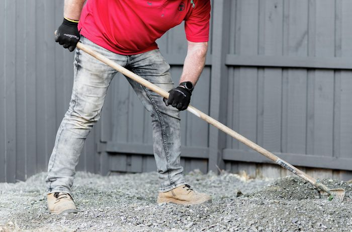 Person spreading out gravel with a rake.