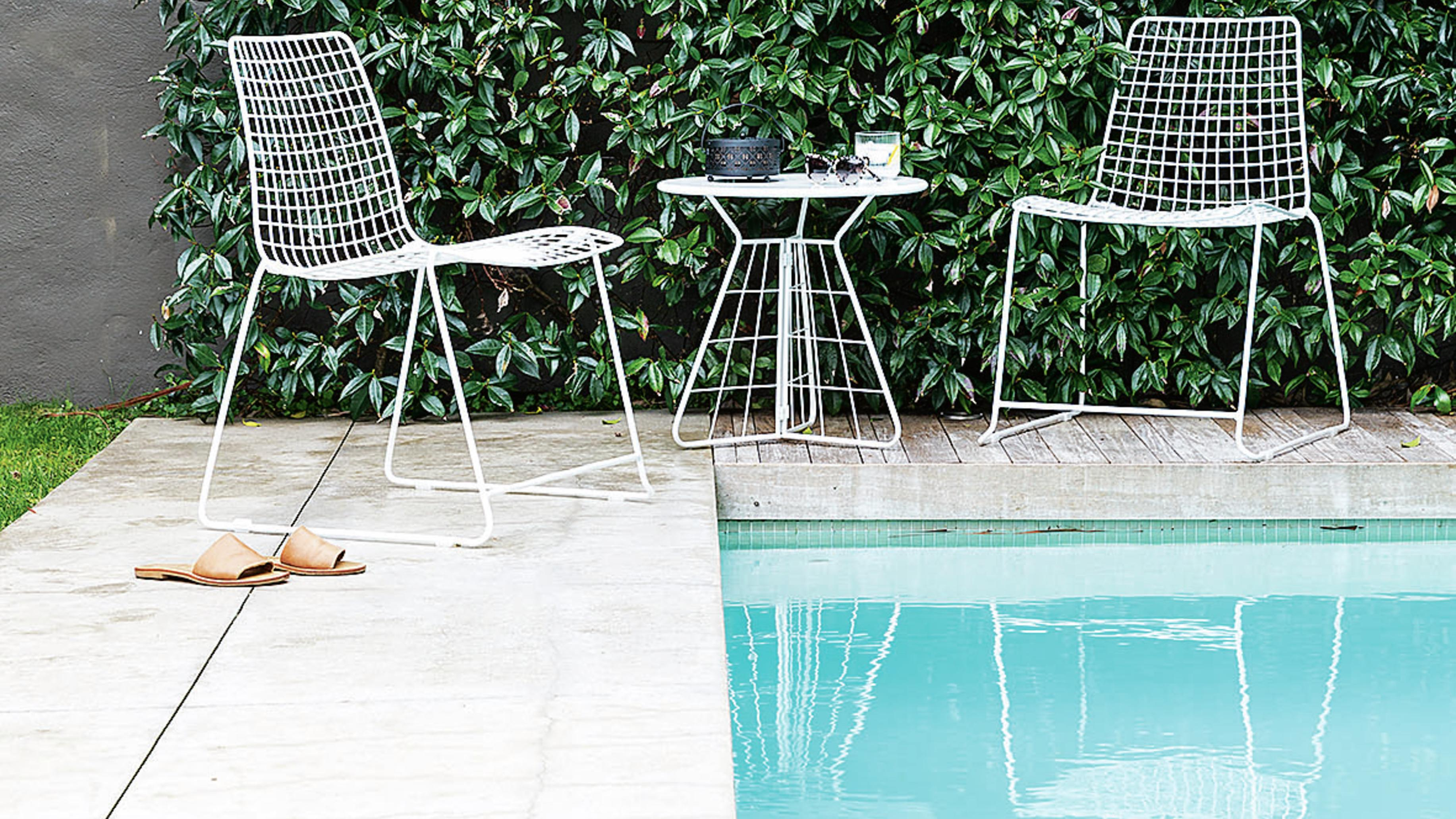 A pool with outdoor tiles and some chairs.