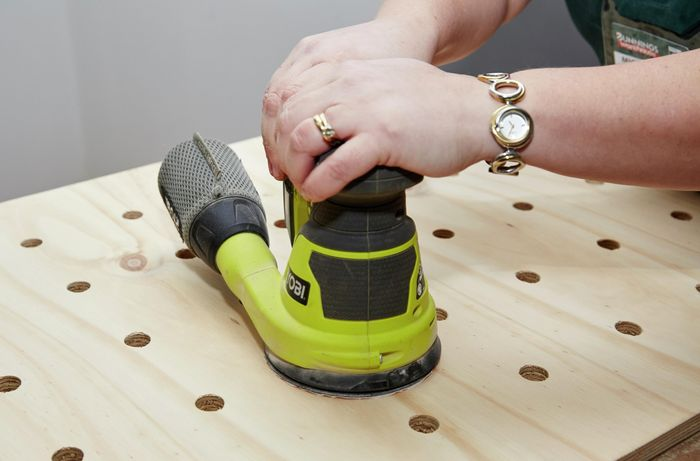A person sanding a sheet of plywood using an orbital sander