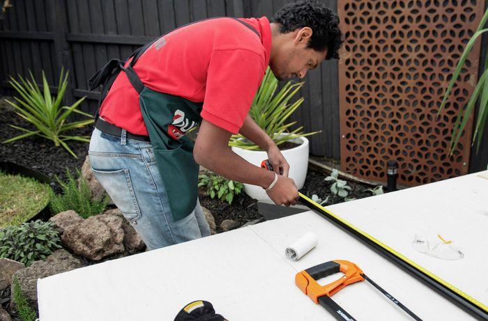 A Bunnings team member measuring a length of metal pipe