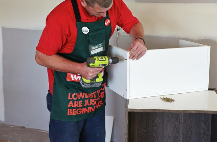 A person attaching the sides of a cabinet using a cordless driver