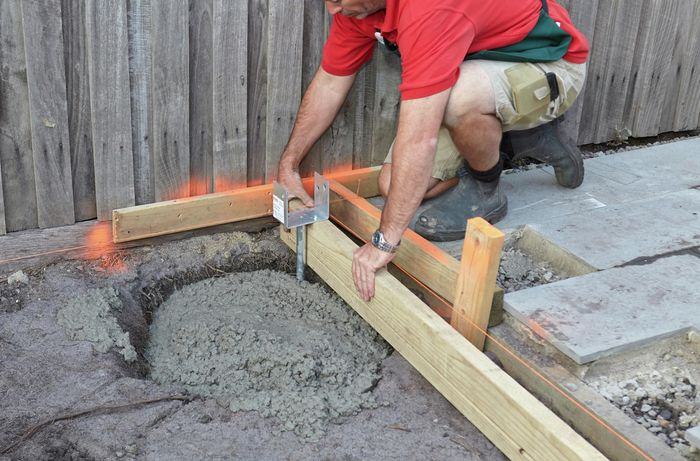 Person filling hole with concrete.