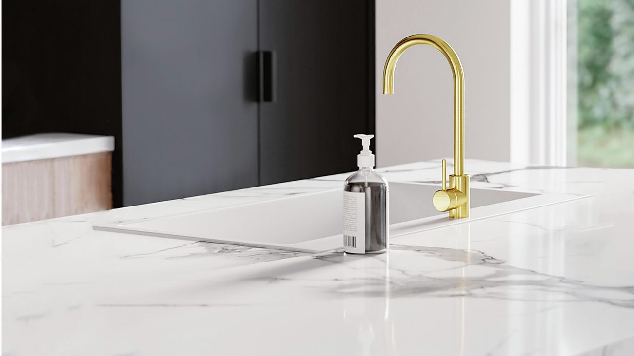 Close up of Kaboodle marble-look kitchen benchtop, sink and brushed brass sink mixer and hand wash