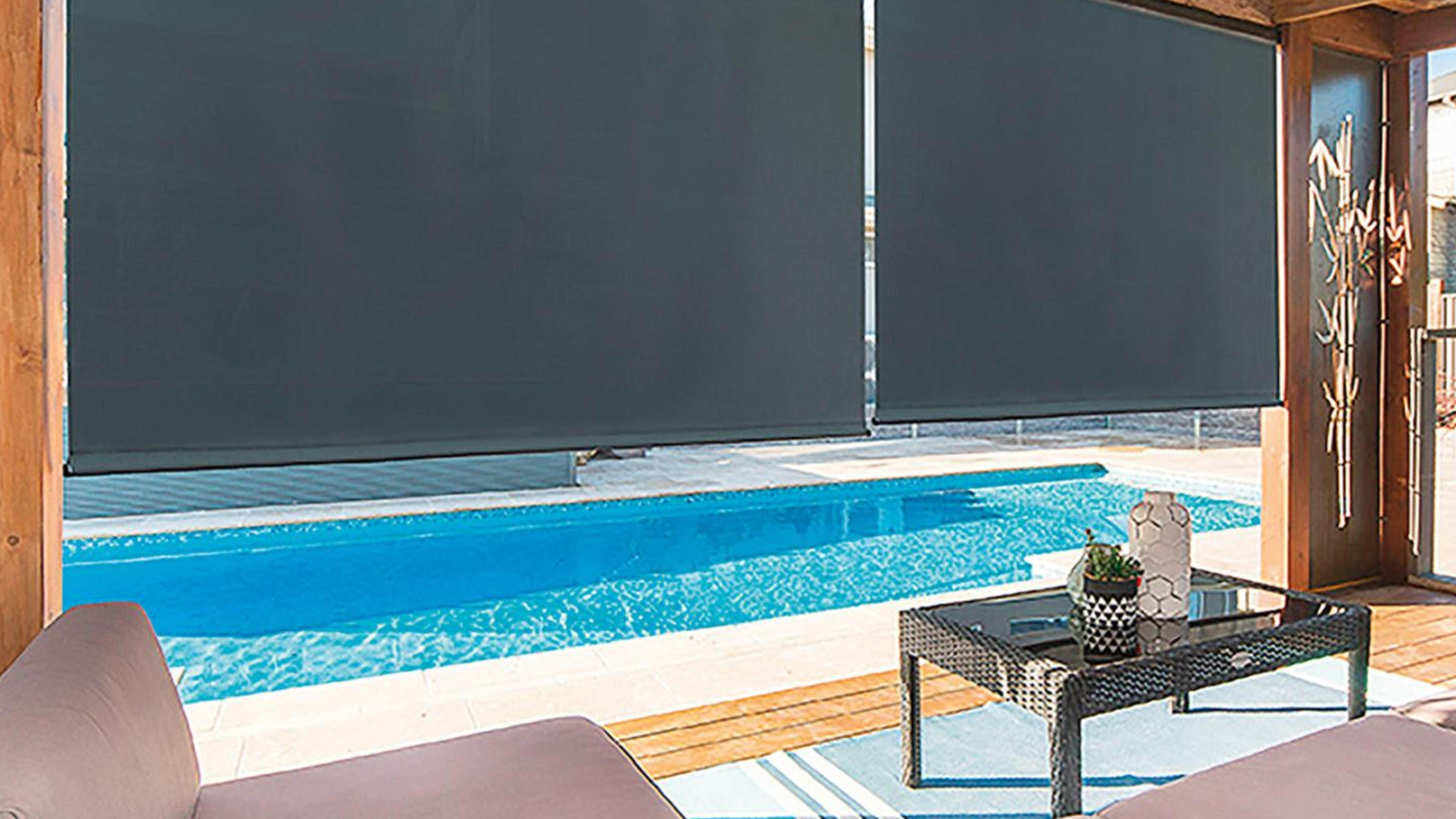 Timber decking by pool with a blind separating the decking area from the pool