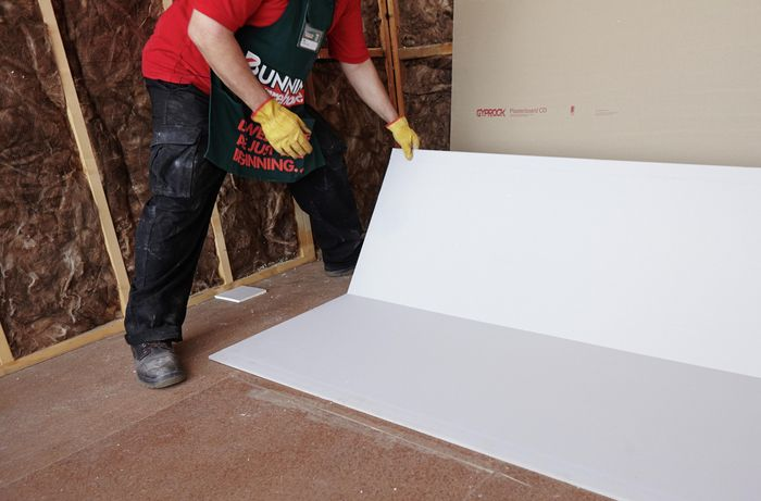A Bunnings team member placing a half-height sheet of plasterboard against a wall