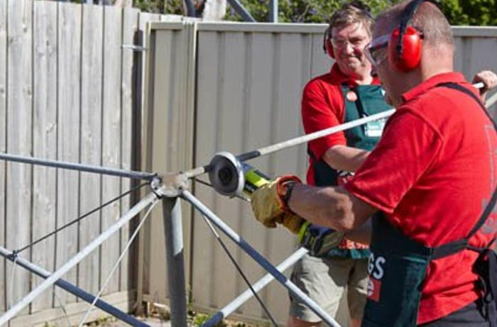 Two Bunnings team members removing the clothesline arms using a compact model angle grinder.