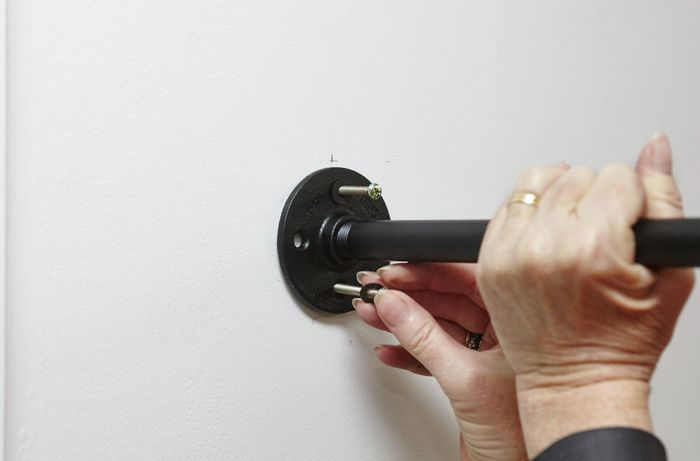 A person inserting screws into shelf support flanges