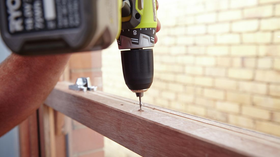 Person using a cordless drill to drill a hole in a sash window frame
