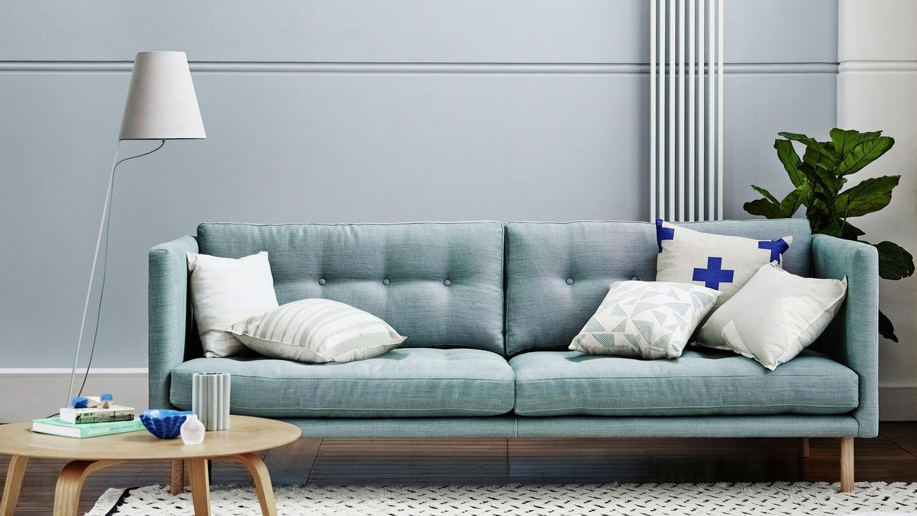 A blue couch in a living room with grey walls.