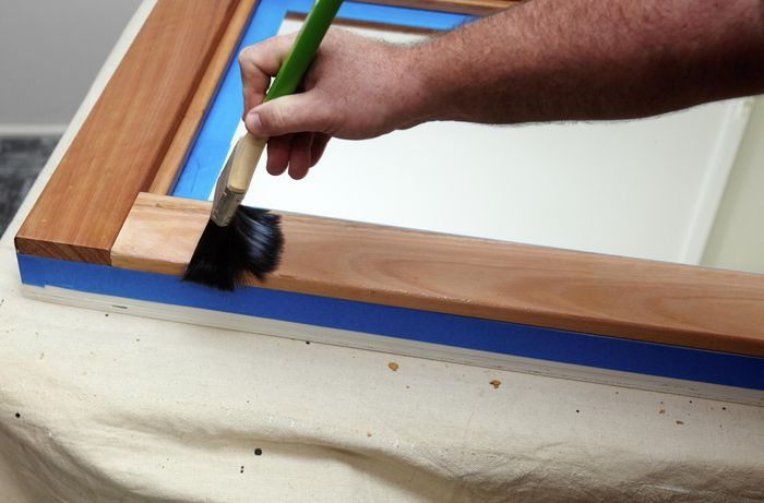 A person varnishing a timber frame with a brush