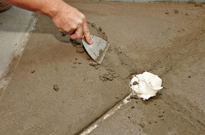 A person using a paint scraper to fill gaps with screed