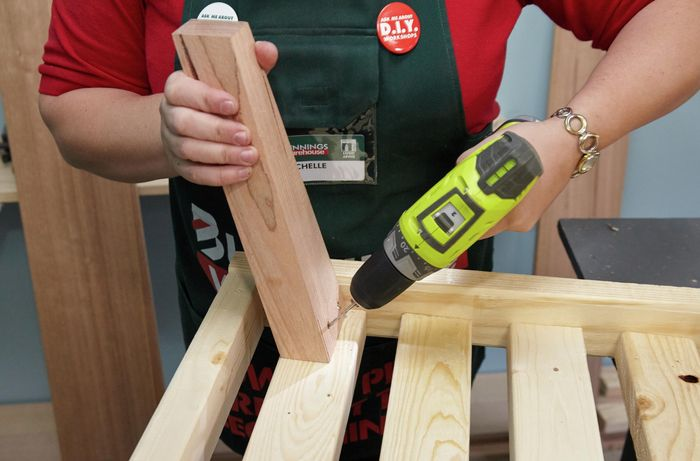 Person drilling timber bed leg into frame