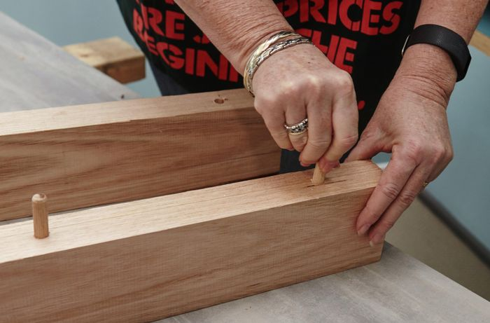 A person inserting dowels into timber