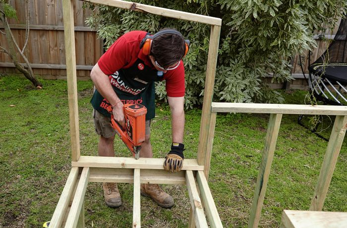 The roosting box base being attached to the supports below by a Bunnings team member with a nail gun