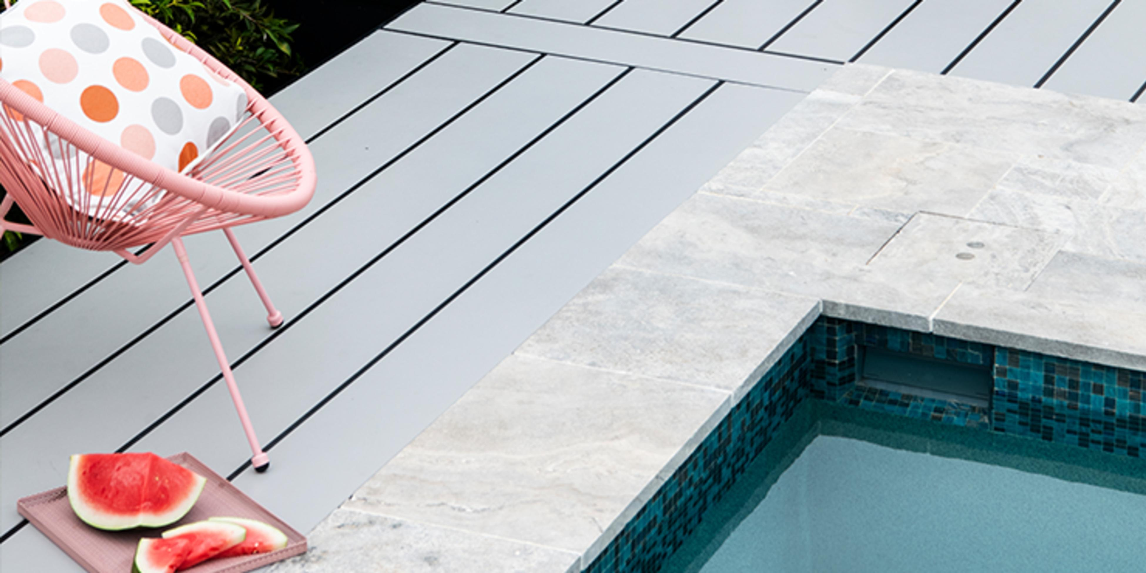 Pool surrounded by timber decking with a pink chair