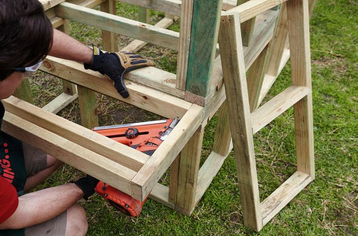 Part of a wooden frame for a chicken coop being nailed into place by a Bunnings team member with a nail gun