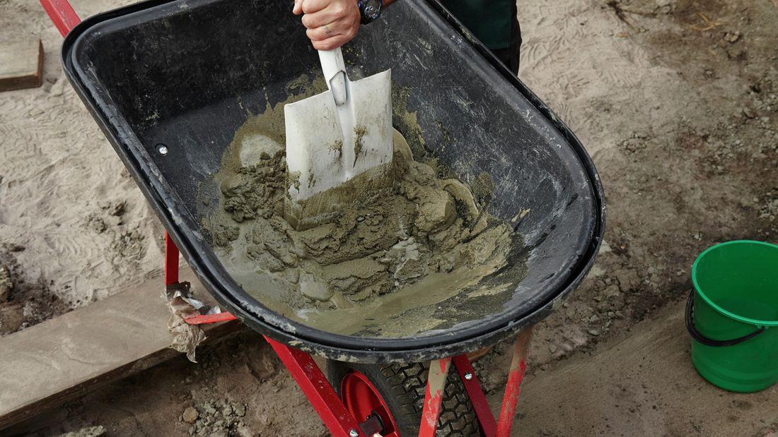 Person mixing mortar in wheelbarrow with shovel.