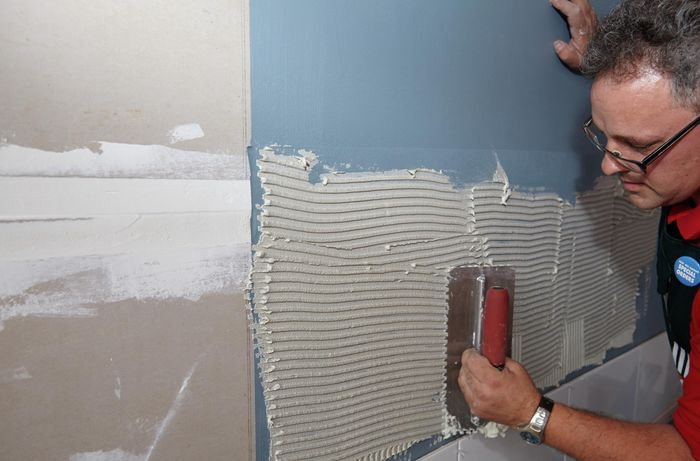 Person using tool to spread tile glue on the wall.