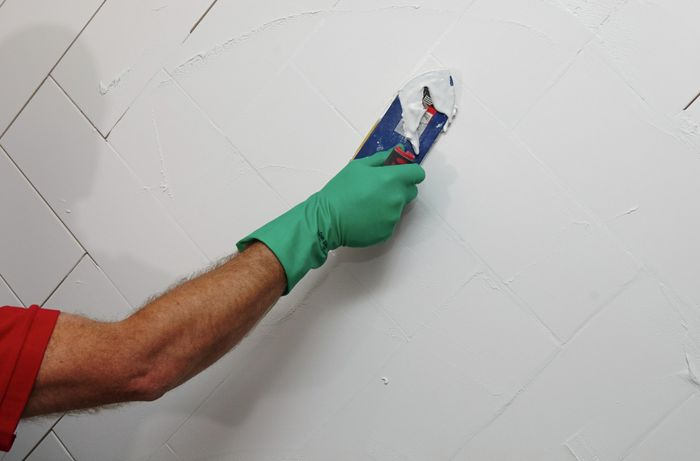 Grout being applied to tiles on a wet wall