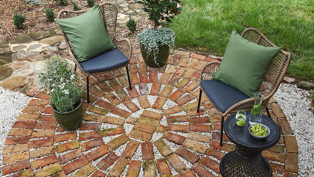 A completed brick paved patio complete with two lounge chairs