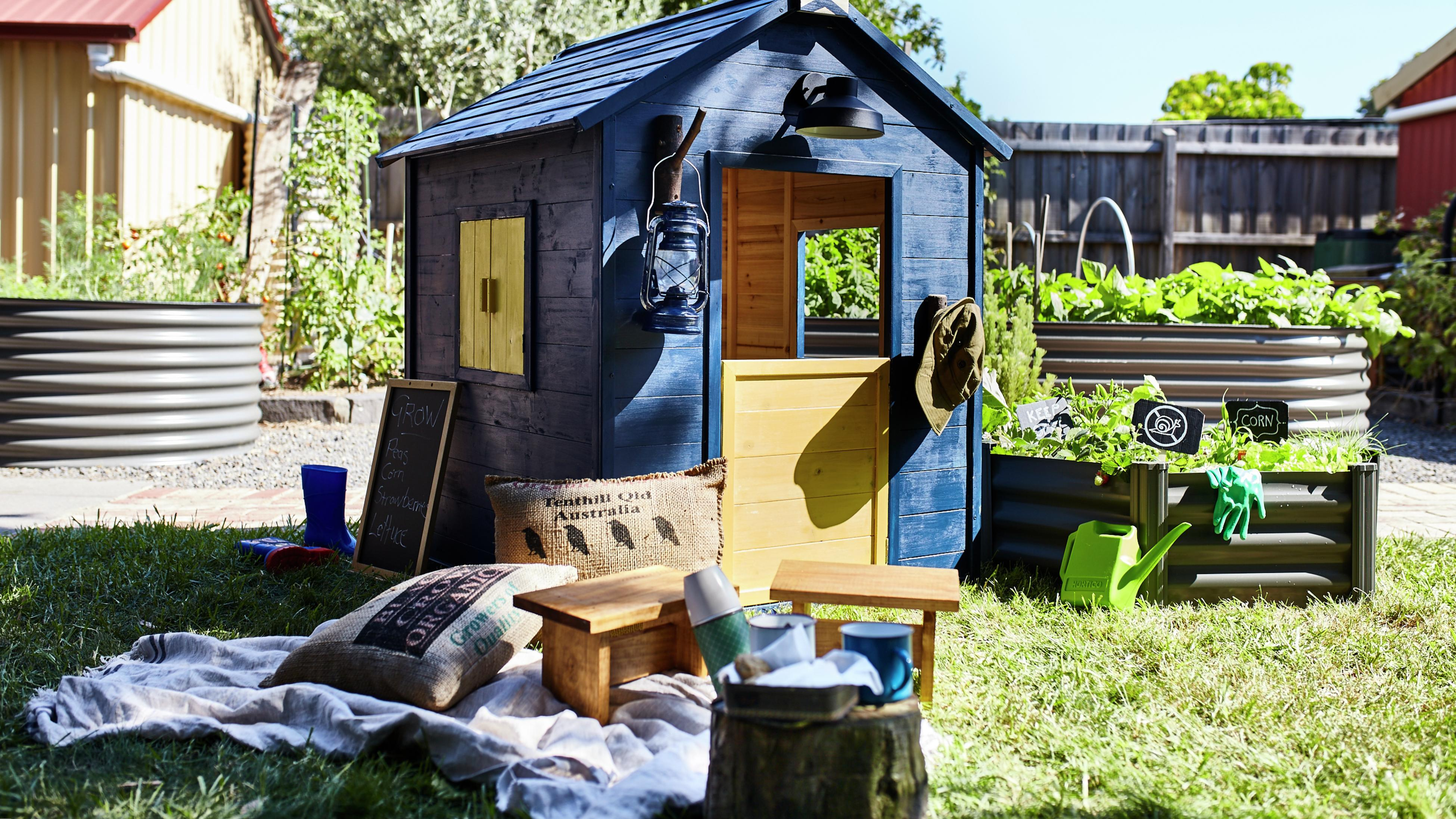 Navy kids cubby house with picnic setup out front.
