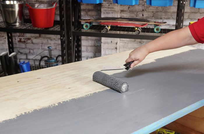 A person painting a plywood benchtop grey using a roller
