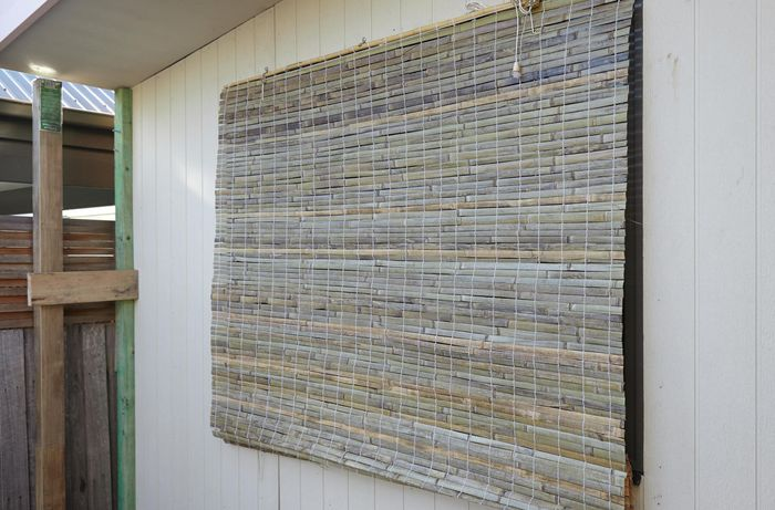 A bamboo blind covering a window on the outside of a house