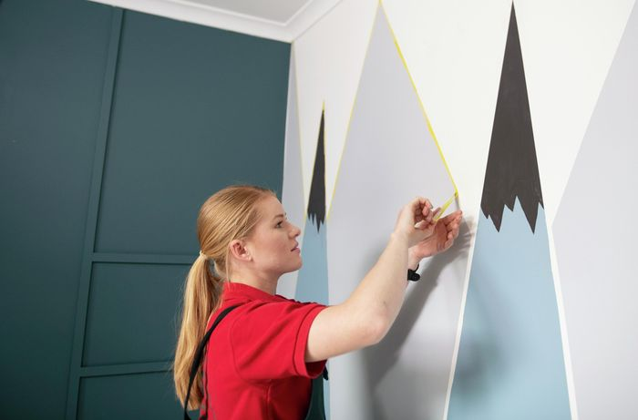 Person peeling tape lines off wall.