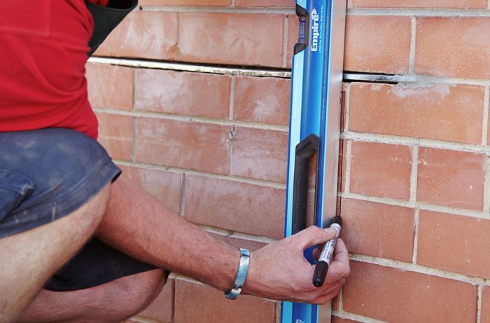 A lintel being installed into a brick wall before cutting into it