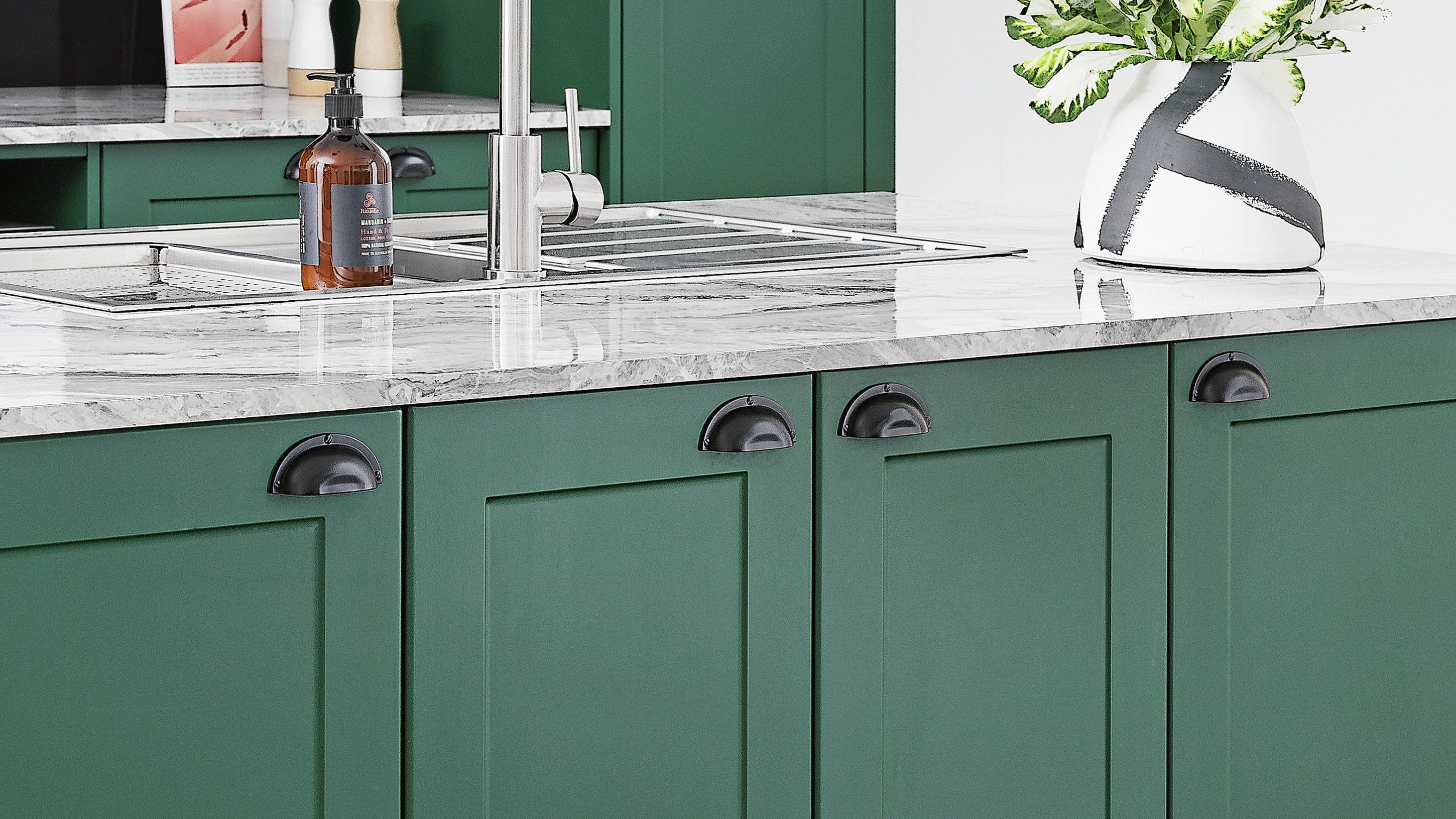 Kitchen island bench featuring marble benchtop, green cabinetry with black handles, and sink.